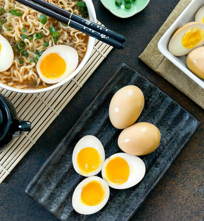 top-down photo of eggs sliced in half with a bowl of ramen
