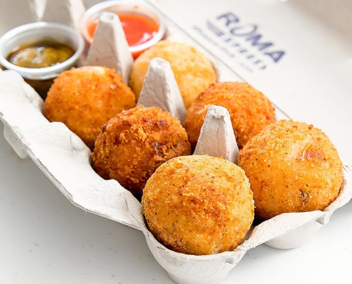 photo of a variety of arrancini with dipping sauces