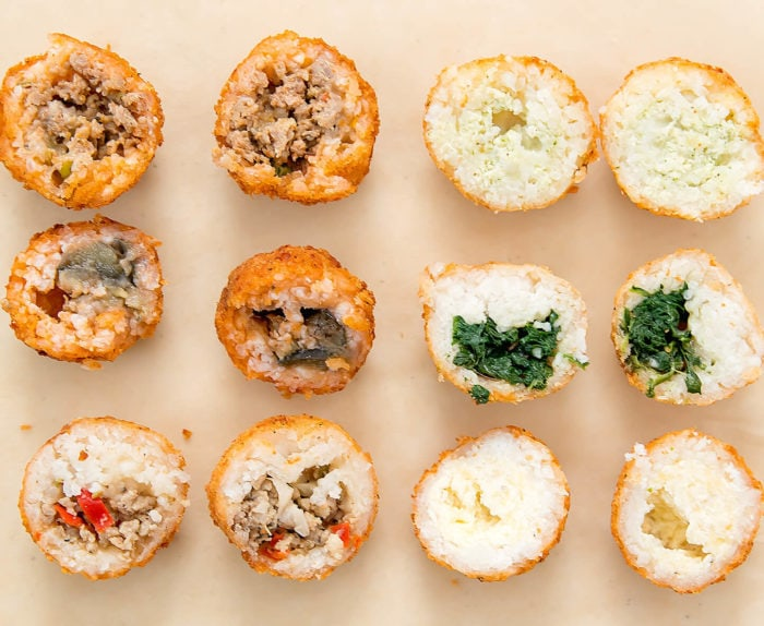overhead photo of different arrancini sliced in half to show the fillings
