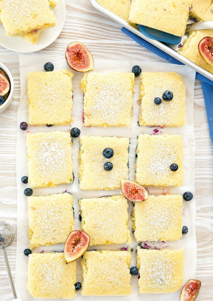 overhead shot of sheet pan pancakes sliced into squares with fresh figs and blueberries