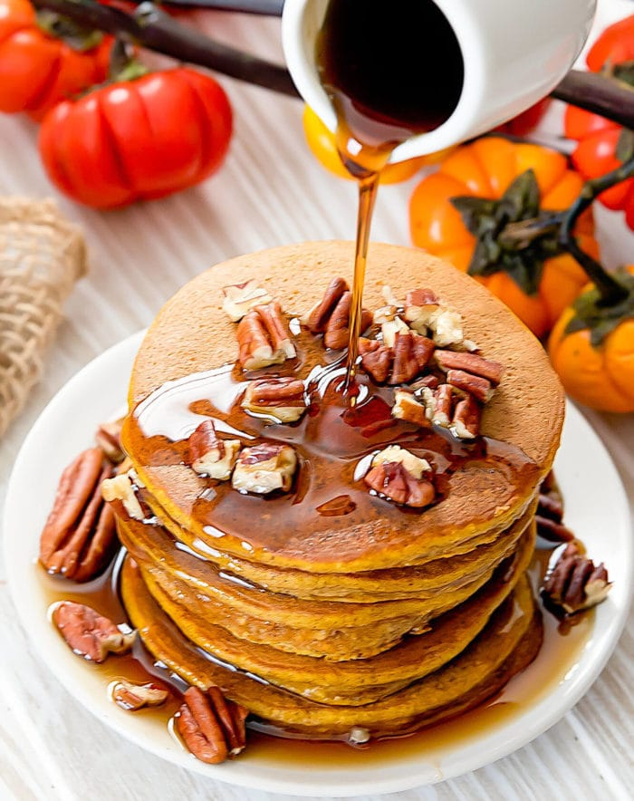 a top-down photo of syrup being poured onto a stack of pancakes topped with walnuts