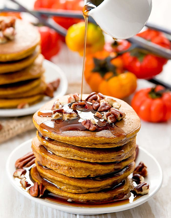 photo of syrup being poured over a stack of flourless pumpkin pancakes