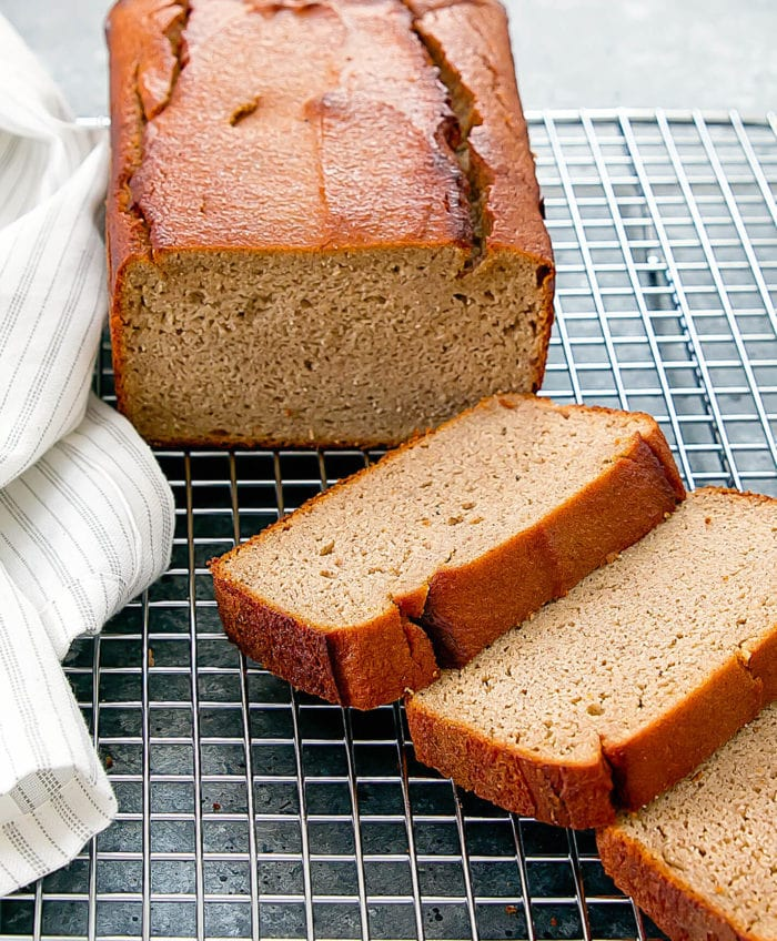 a loaf of flourless banana bread with three slices on a baking rack