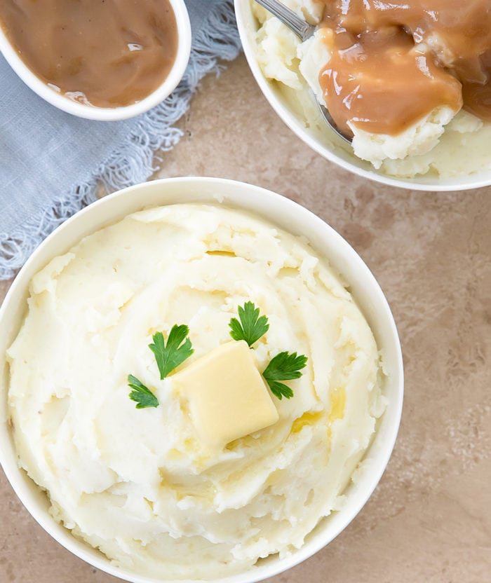 one bowl of Instant Pot mashed potatoes garnished with butter with a ladle of gravy on the side