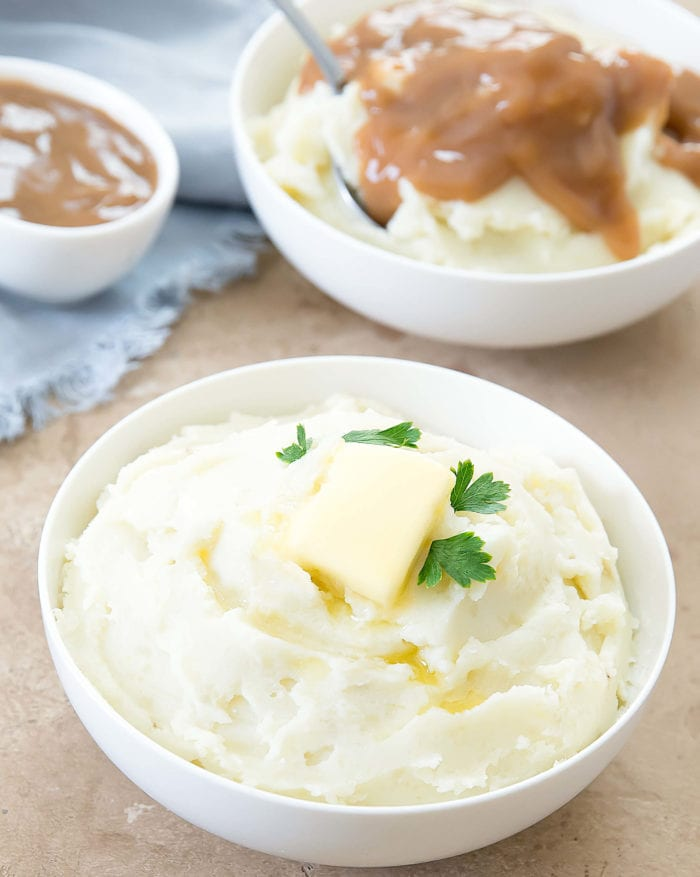 one bowl of Instant Pot mashed potatoes with butter and another bowl garnished with gravy in the background