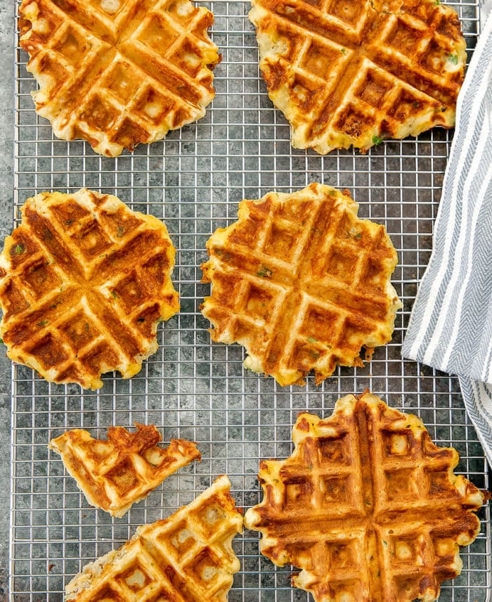 a top-down photo of mashed potato waffles on a baking rack