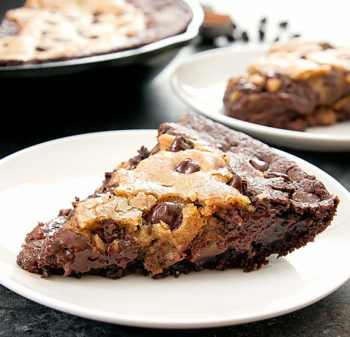 photo of a slice of Skillet Brownie Chocolate Chip Cookie on a white plate