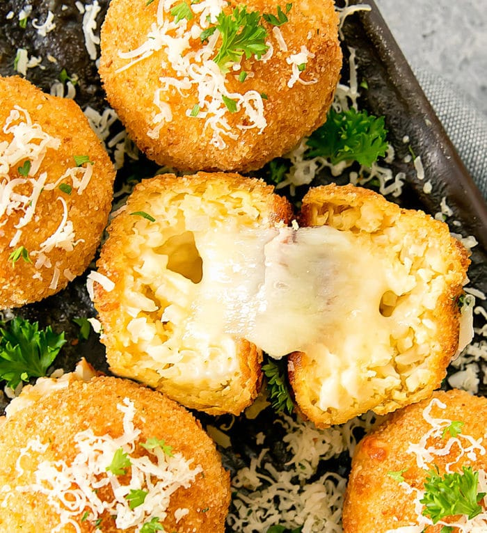 close-up photo of a cauliflower arrancini sliced in half to show the melted cheese center