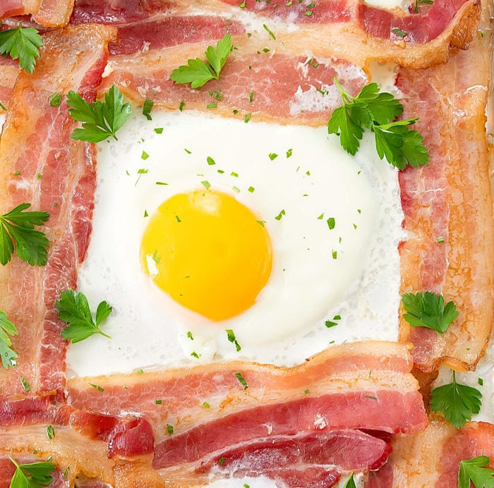 overhead photo of one egg with bacon on a sheet pan