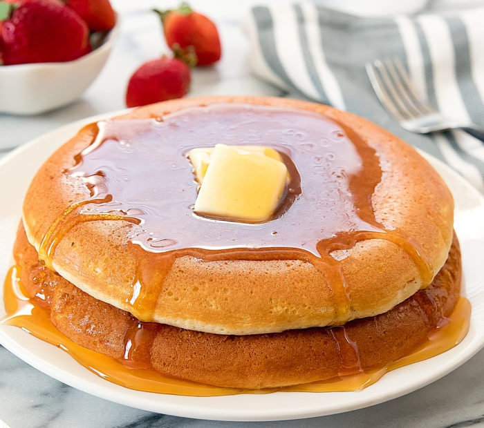 a stack of two large souffle pancakes topped with butter and syrup.