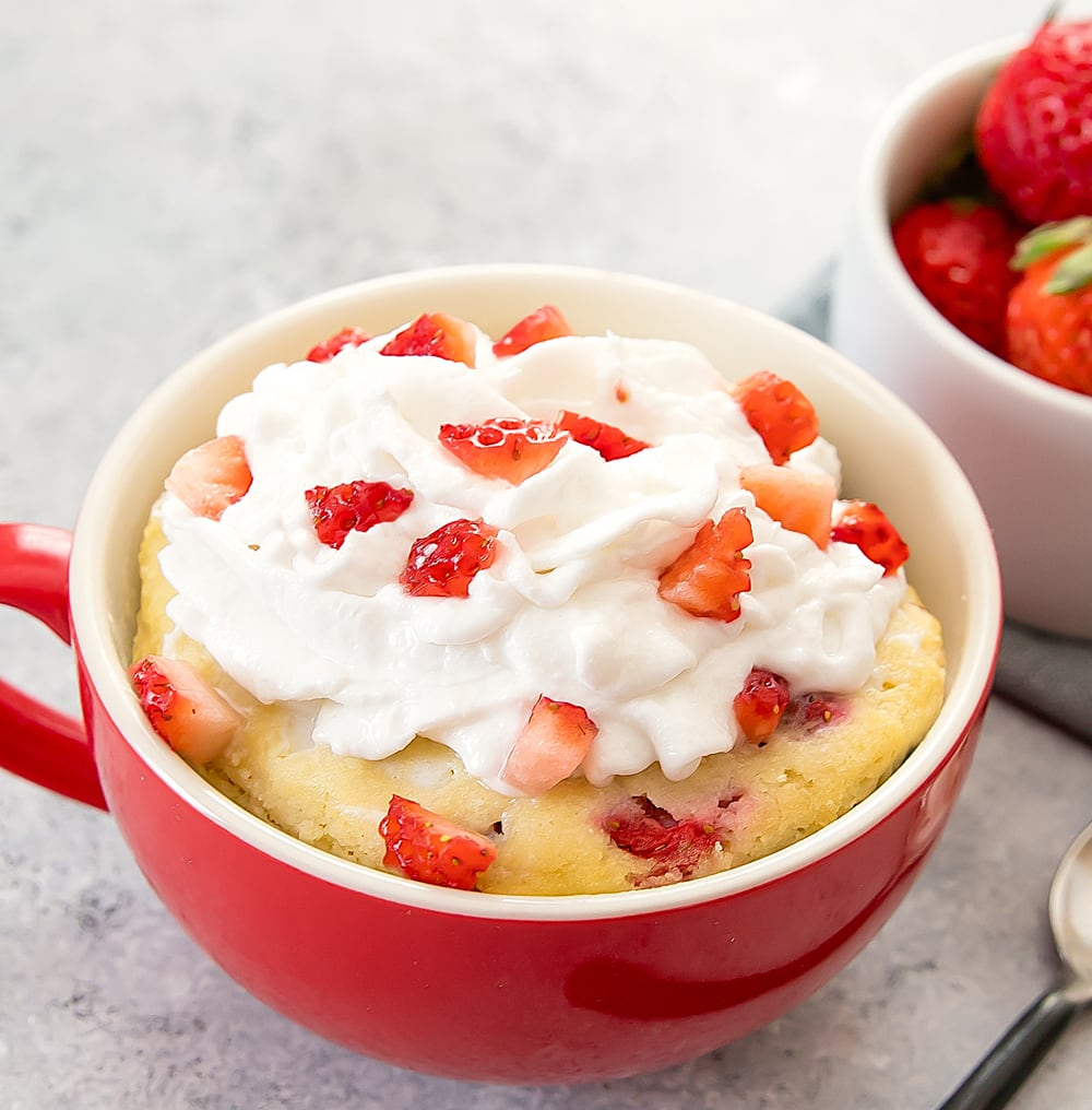 photo of Strawberries and Cream Mug Cake garnished with whipped cream and chopped strawberries