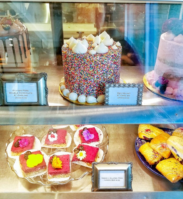 photo collage of different desserts in the display case inside the cafe