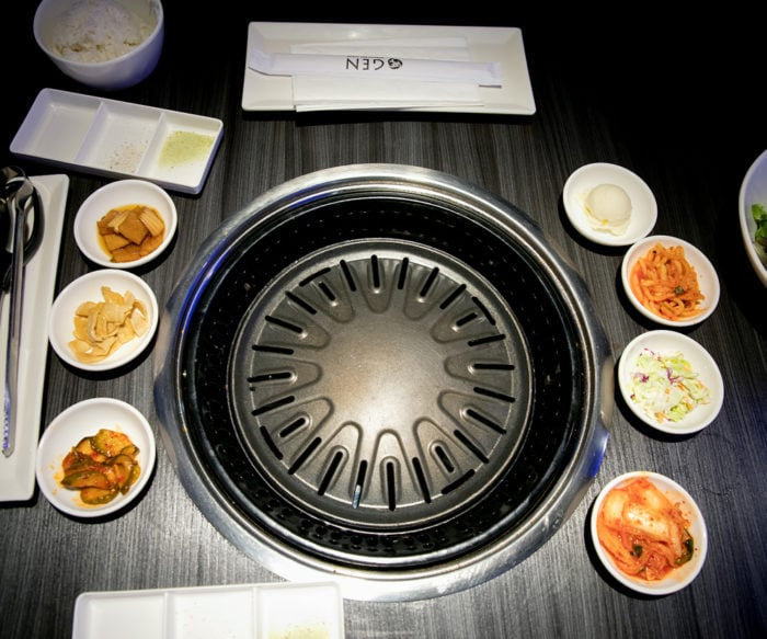 photo of the table grill with different food items around it in small bowls