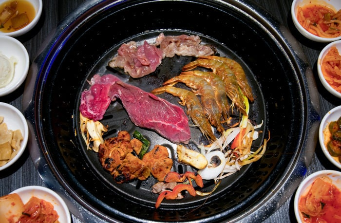 overhead photo of table grilled filled with different meats at Gen Korean BBQ House