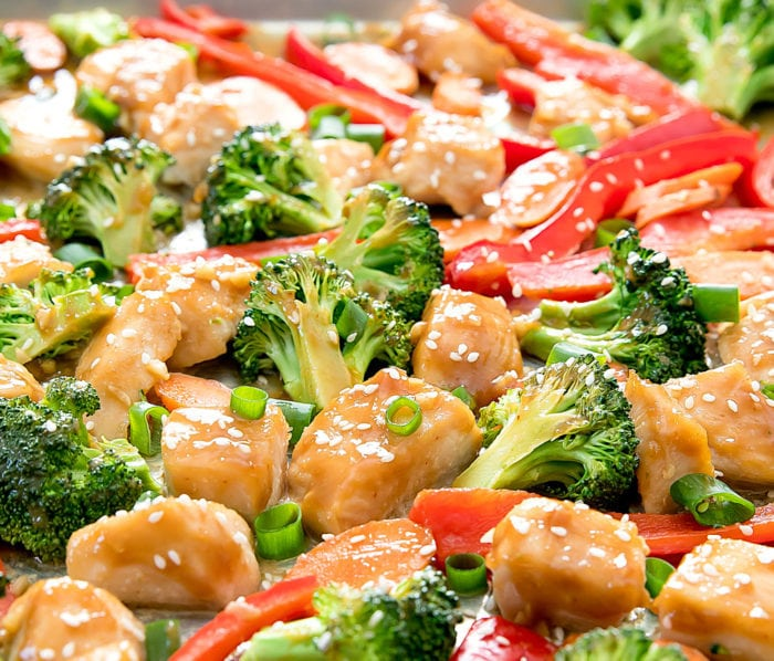 close-up of honey garlic chicken garnished with sliced green onions and sesame seeds