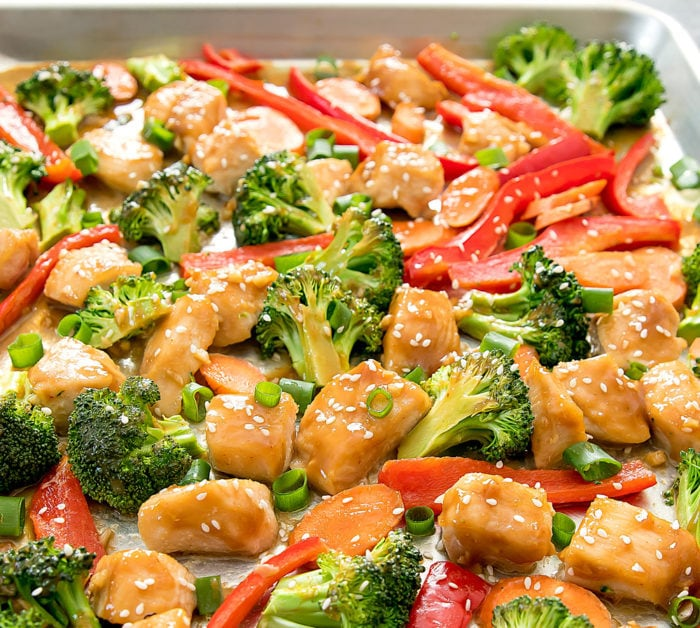 a close-up of honey garlic chicken with broccoli and red bell peppers on a sheet pan