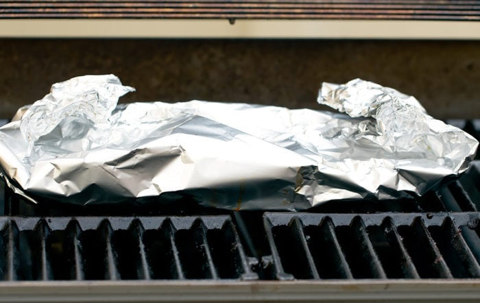 step by step photo of ribs wrapped in foil on the grill