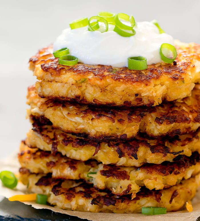 close-up photo of a stack of Cauliflower Fritters topped with sour cream