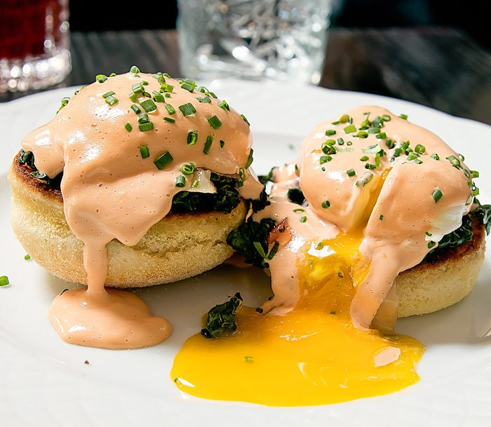 close-up photo of Jamon Iberico Benedict, English Muffin, Poached Eggs, Braised Kale, Smoked Tomato Hollandaise