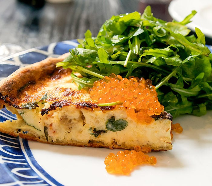 photo of a slice of Crab Quiche, Roasted Red Onion, Herbs, Caviar, Everything Crust