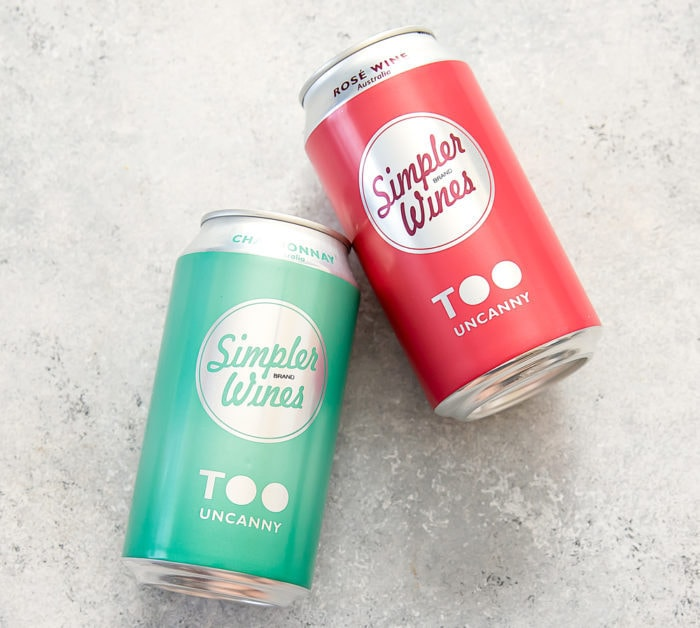 photo of two cans of Simpler Wines Too Uncanny