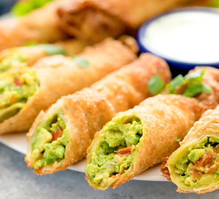 View of avocado egg rolls, cut open to show filling