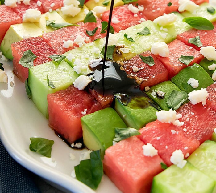 Pouring balsamic dressing on the avocado watermelon salad
