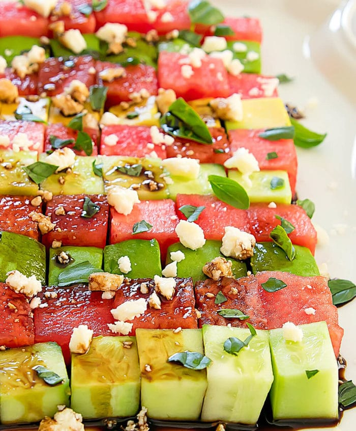 Avocado watermelon salad garnished with feta cheese and fresh herbs