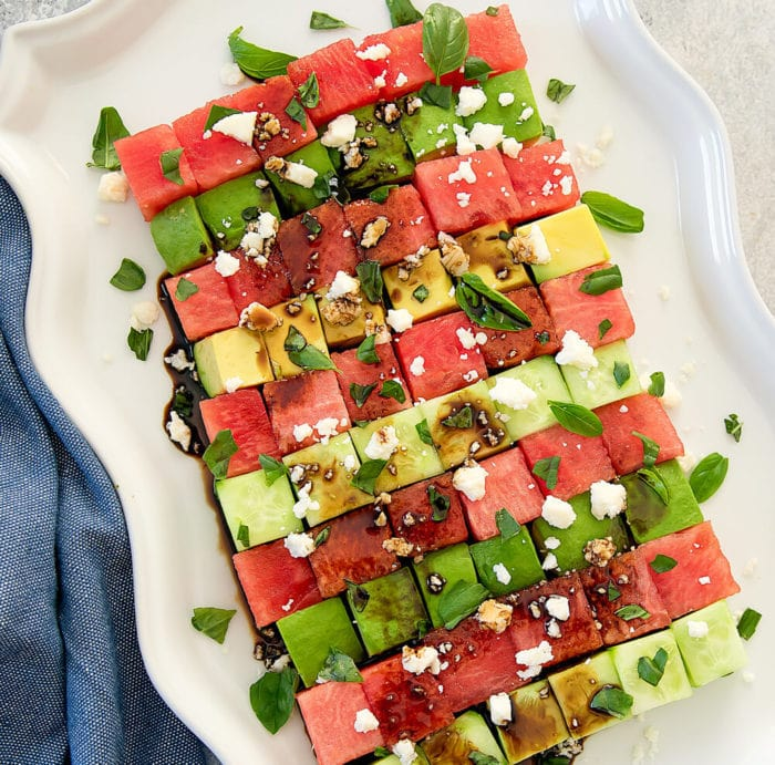 overhead photo of an Avocado watermelon salad on a white serving platter