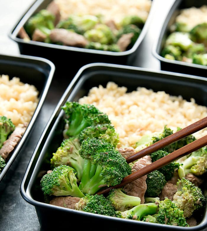 close-up photo of chopsticks holding a piece of broccoli