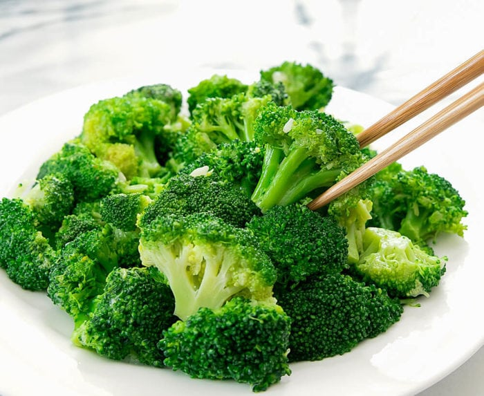 garlic broccoli stir fry on a plate with chopsticks