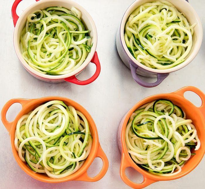 overhead photo of four small baking dishes filled with zucchini noodles