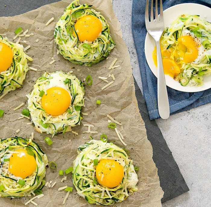 overhead photo of zucchini egg nests with one on a plate that has a runny yolk