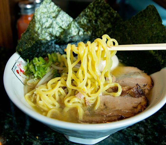 photo of chopsticks holding wavy egg noodles