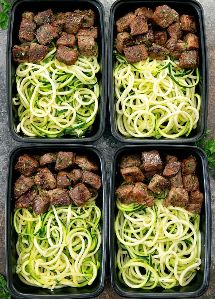overhead photo of four meal prep containers with Garlic Butter Steak Bites with Zucchini Noodles