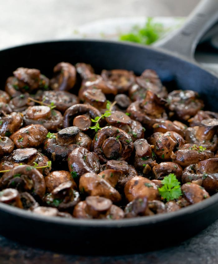 close-up photo of garlic mushrooms in a cast iron skillet