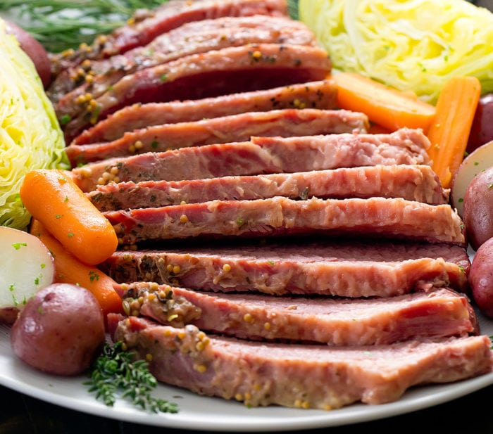 close-up photo of sliced corned beef on a platter with vegetables