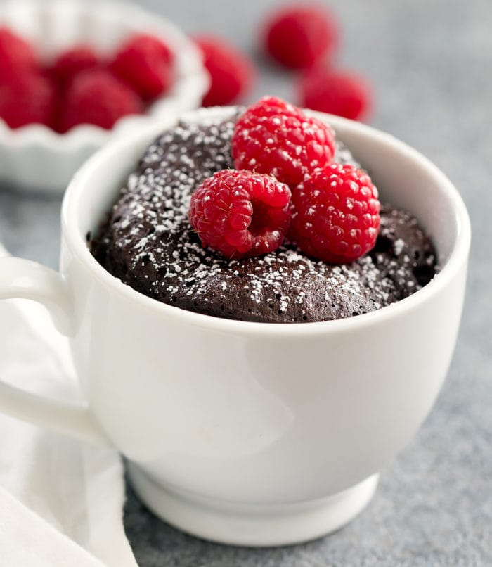 close-up photo of a keto chocolate mug cake topped with fresh raspberries