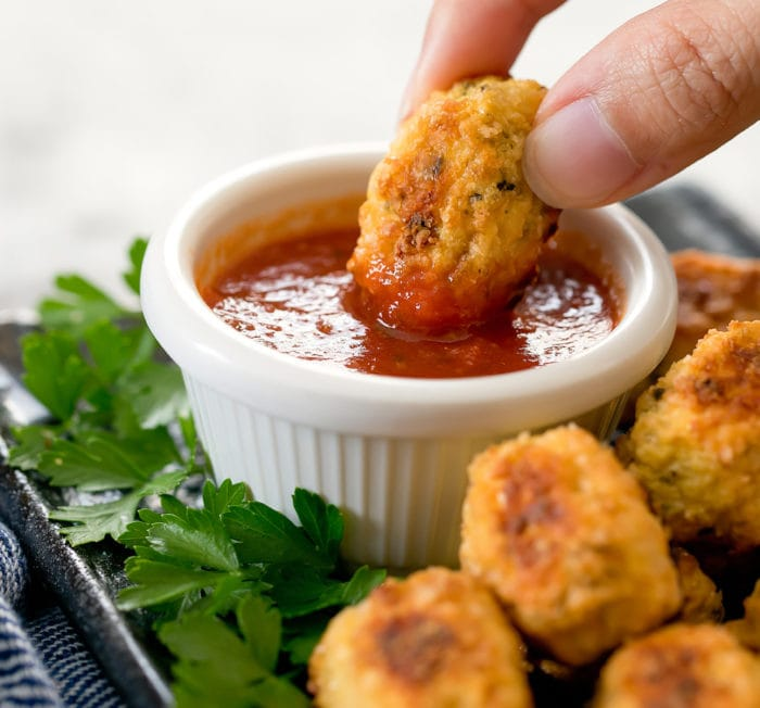 photo of a cauliflower tot being dipped in sauce