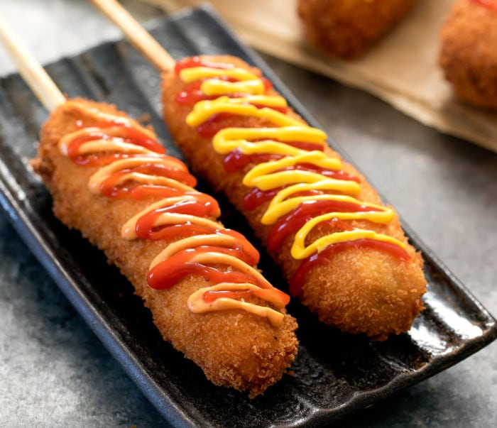 close-up photo of two korean hot dogs drizzled with sauces