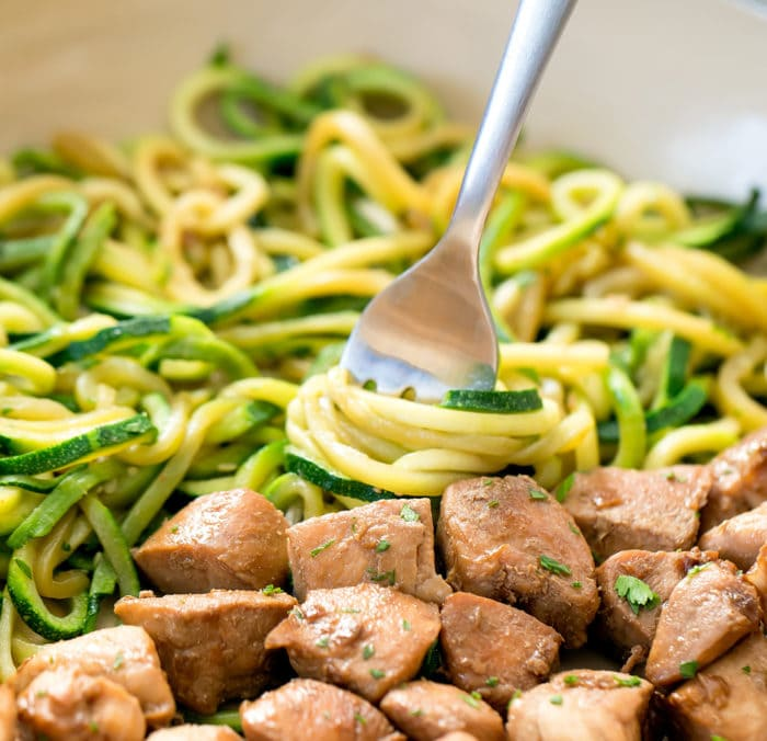 close up photo of a fork twirling zucchini noodles with garlic butter chicken