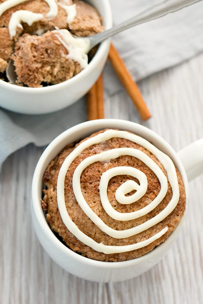 overhead photo of a cinnamon roll mug cake with another one in the background