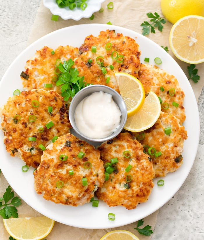 overhead photo of chicken fritters on a plate with dipping sauce and lemon wedges