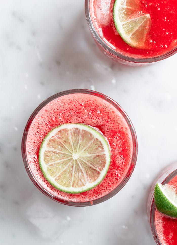 overhead photo of a glass watermelon juice garnished with lime