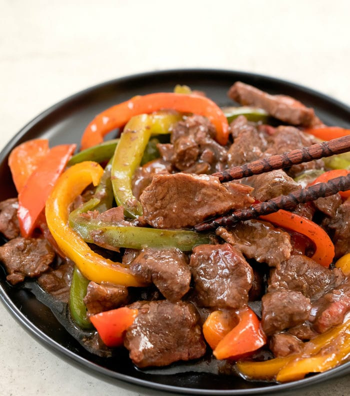 close-up photo of a plate of pepper steak with chopsticks