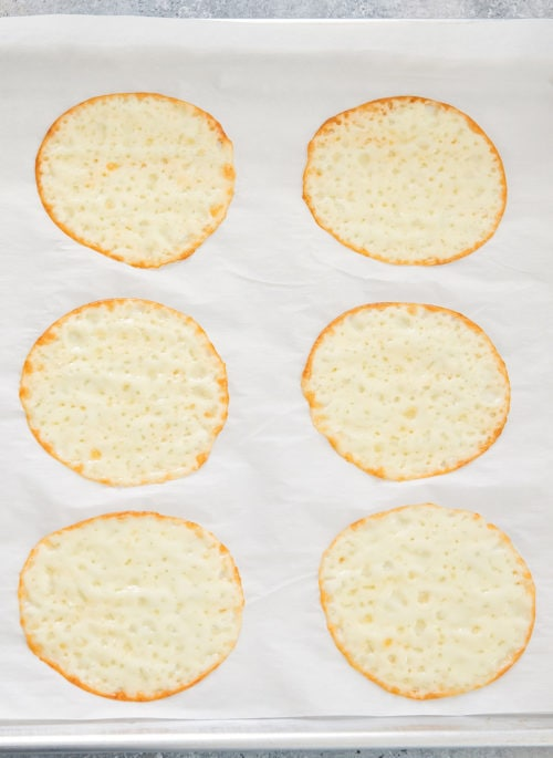 overhead photo of cheese rounds on a baking sheet