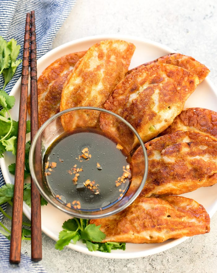 overhead photo of a plate of pot stickers with sauce and chopsticks