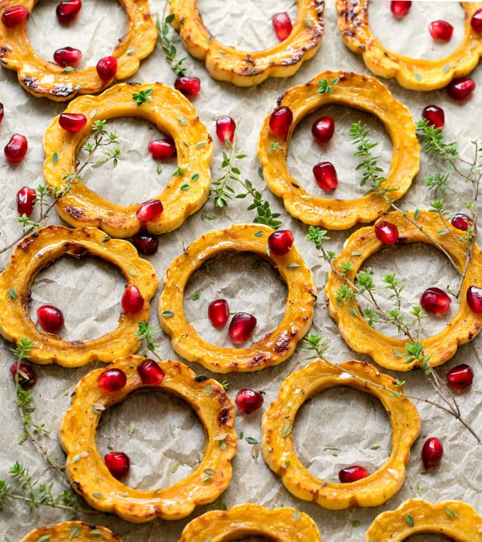 overhead photo of squash rings on parchment with pomegranate seeds