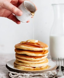 syrup being poured on a stack of pancakes