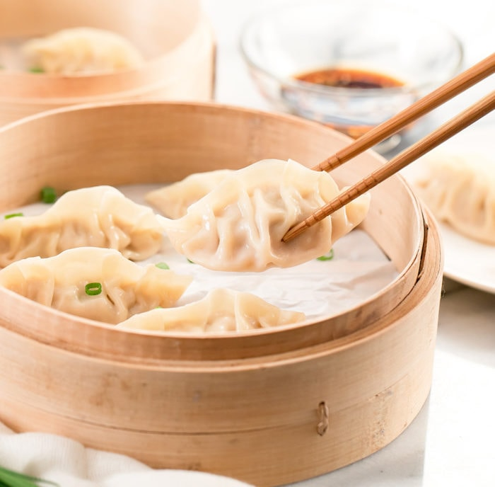 photo of chopsticks holding a dumpling with more in a steamer